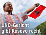 Ein Mann schwenkt eine Kosovo-Fahne