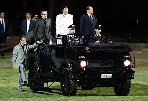 Berlusconi und Al-Gaddafi stehend in einem fahrenden Jeep