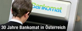 Ein Kunde hebt von einem Bankomat Bargeld ab.