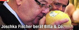 Joschka Fischer riecht an einer Melone.