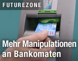 Jemand steckt Bankomatkarte in bankomatschlitz