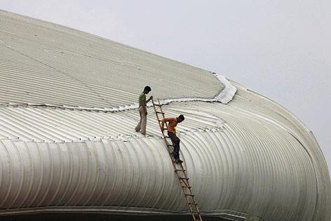 Indische Arbeiter auf dem Dach des Jahawarial Nehru Stadions