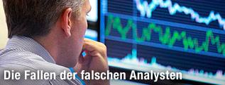 Börsenmakler vor einem Bildschirm mit Börsencharts