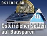 Haus mit einem Münzschlitz im Dach und einer darin steckenden Euro-Münze