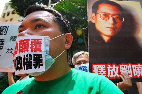 Demonstrant in Hongkong mit beschriftetem Mundschutz und einem Plakat von Liu Xiabao im Hintergrund