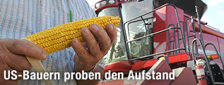 Amerikanischer Farmer mit einem Maiskolben in der Hand und einem Mähdrescher im Hintergrund