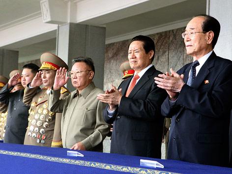 Kim Jong Un salutiert während er mit seinem Vater Kim Jong Il der Militärparade beiwohnt.