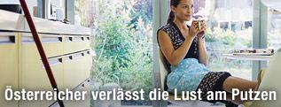 Eine Frau trinkt gemütlich einen Kaffee und der Wischmop steht unberührt in der anderen Ecke der Küche