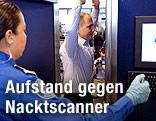 Eine Sicherheitsbeamtin steht vor einem Mann im Nacktscanner.