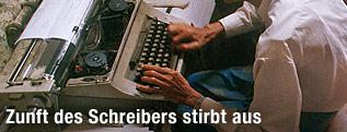Mann schreibt auf einer Schreibmaschine