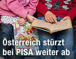 Zwei Kinder lesen in einem Buch