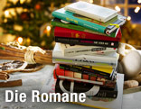 Ein Stapel Bücher liegt auf einem weihnachtlich geschmückten Tisch