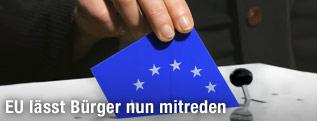 Mann steckt ein blaues Kuvert mit EU-Sternen in eine Urne