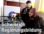 Zwei Personen in einem Wahllokal im Kosovo