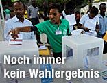 Wähler in Haiti, die gerade ihre Wahlkarte in die Urne werfen