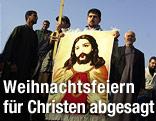 Irakische Christen halten eine Bild von Jesus in der Hand