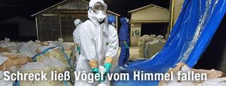 Arbeiter mit Seuchen-Schutzgewand tragen Säcke