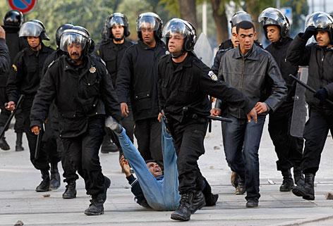 Tunesische Polizisten schleifen Demonstranten über die Straße