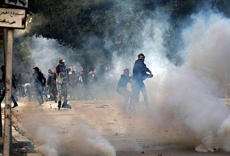 Demonstranten werden Steine gegen die Polizei