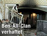 Mann trägt Bilderrahmen aus dem Haus des Schwägers von Ben Ali