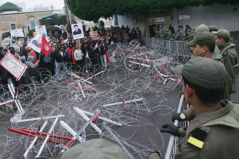 Demonstranten stehen vor einer polizeilichen Absperrung