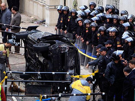 Polizisten hinter einer Absperrung sichern die Anschlagstelle mit einem zerstörten Auto.