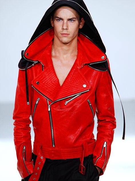 Model mit knalliger, roter Lederjacke mit Ausschnitt und Kapuze