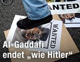 Demonstrant steht auf einem Bild von Al-Gaddafi