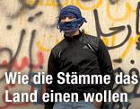 Demonstrant steht vor einer Graffitiwand