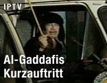 Der libyische Staatsführer Muammar al-Gaddafi spricht aus einem Auto mit einem weißen Regenschirm in der Hand