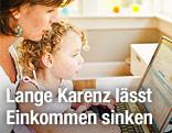 Frau mit Kind vor Laptop