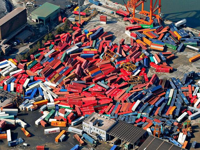 Container liegen im Hafen Sendai auf einem Haufen