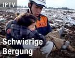 Rettungshelfer mit Kind im Arm
