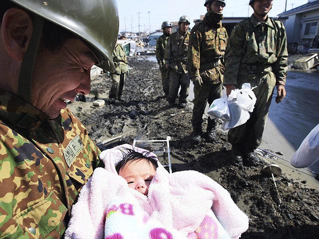 Soldat in Ishinomaki hält gerettetes Baby in der Hand