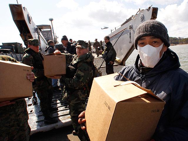US-Soldaten und Einwohner entladen Hilfsgüter