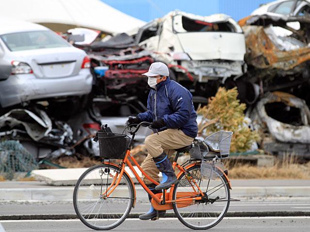 Ein Radfahrer fährt an einem Berg von Autowracks vorbei.
