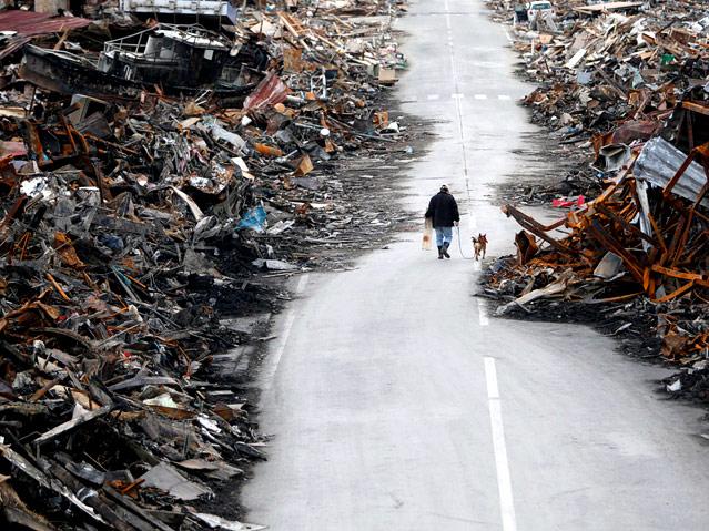 Mann geht mit Hund auf von Schutt freigeräumter Straße