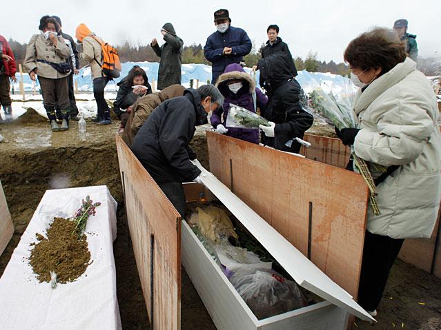 Angehörige in Higashi-Matsushima beerdigen ein Opfer der Erdbeben- und Tsunamikatastrophe.