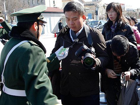 Journalist wird von chinesischen Polizisten überprüft