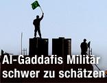 Libyscher Soldat hält eine libysche Flagge in die Luft