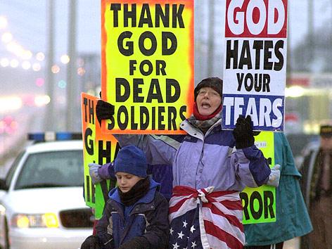 """Ein Mitglied der Westboro Baptistenkirche hält Schilder mit der Aufschrift """"Thank God for dead Soldiers"""" und """"God hates your tears""""."""