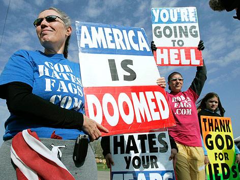 """Ein Mitglied der Westboro Baptistenkirche hält Schilder mit der Aufschrift """"America is doomed"""" und """"You're going to hell"""""""