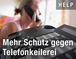 Frau mit Telefonhörer vor Telefon