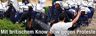Ein Regierungsgegener gestikuliert vor mehreren Polizisten
