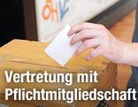 Eine Hand wirft einen Zettel in eine Wahlurne mit einem ÖH-Logo im Hintergrund.