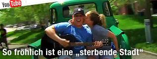 Mann mit Gitarre wird von Frau auf die Wange geküsst
