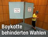Frau kommt aus Wahlzelle heraus