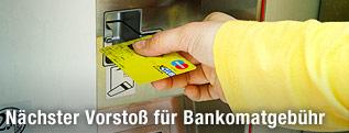 Hand steckt eine Karte in den Bankomat