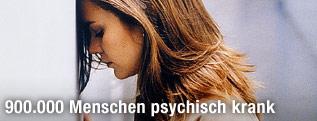 Depressive Frau lehnt ihren Kopf gegen eine Wand