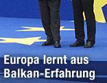 Zwei Männer stehen auf einem EU-Podest mit Sternen